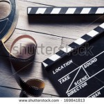 stock-photo-movie-clapper-and-film-reel-on-a-wooden-background-169841813