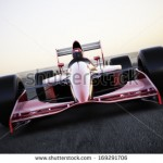 stock-photo-race-car-racing-on-a-track-front-view-with-motion-blur-169291706