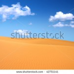 stock-photo-sand-dunes-and-cumulus-clouds-over-them-focus-set-in-foreground-42751141