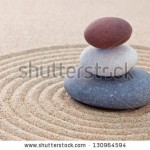 stock-photo-three-pebbles-stacked-on-a-circular-raked-zen-garden-130964594
